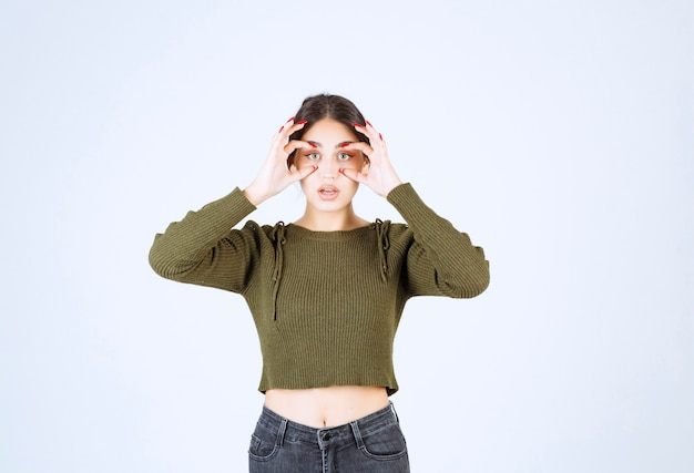 Un modèle de jeune femme charmante avec des yeux jumelles debout sur fond blanc