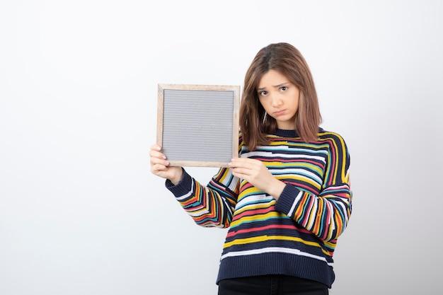 Modèle de jeune femme debout et pointant vers un cadre.