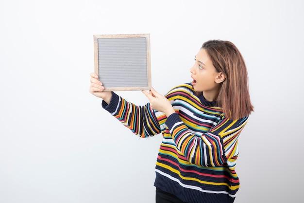 Modèle de jeune femme debout et tenant un cadre.