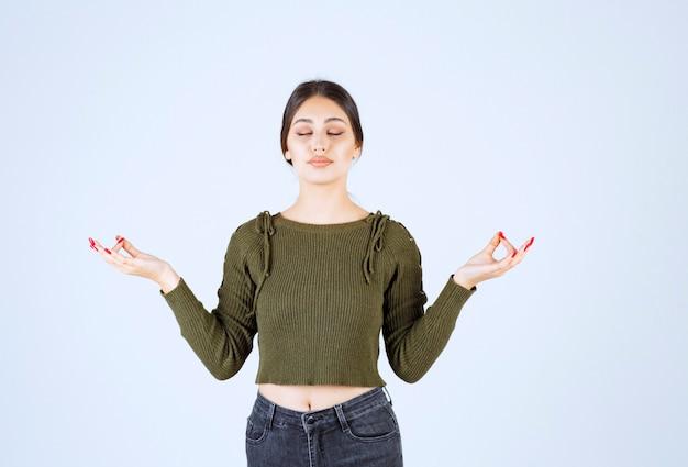 Un modèle de jeune femme détendue debout et méditant.