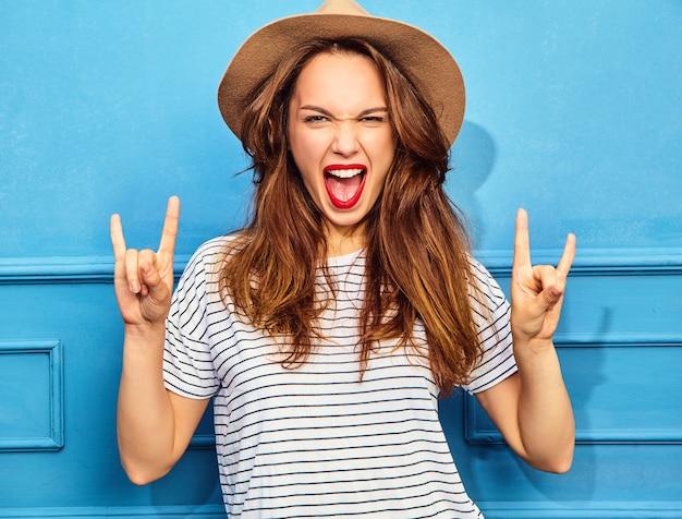 Modèle de jeune femme élégante dans des vêtements d'été décontractés et un chapeau brun avec des lèvres rouges, posant près du mur bleu. crier et montrer le signe du rock and roll