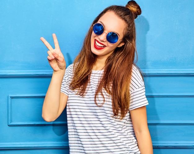 Modèle de jeune femme élégante dans des vêtements d'été décontractés avec des lèvres rouges, posant près du mur bleu. montrant le signe de la paix