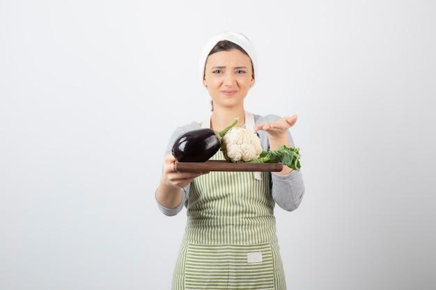 Un modèle de jeune femme mignonne tenant une assiette en bois avec des aubergines et du chou-fleur