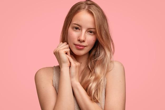 Modèle de jeune femme mignonne tient les mains près du visage, a une peau saine et pure, regarde sérieusement