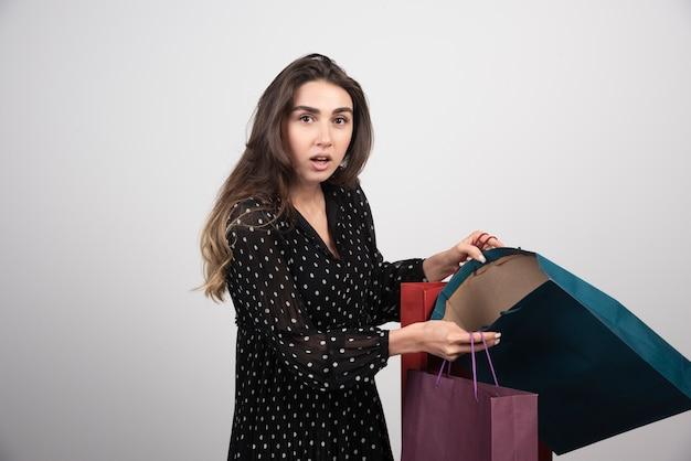 Modèle de jeune femme portant beaucoup de sacs à provisions