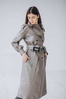 Modèle jeune femme portant un long manteau gris