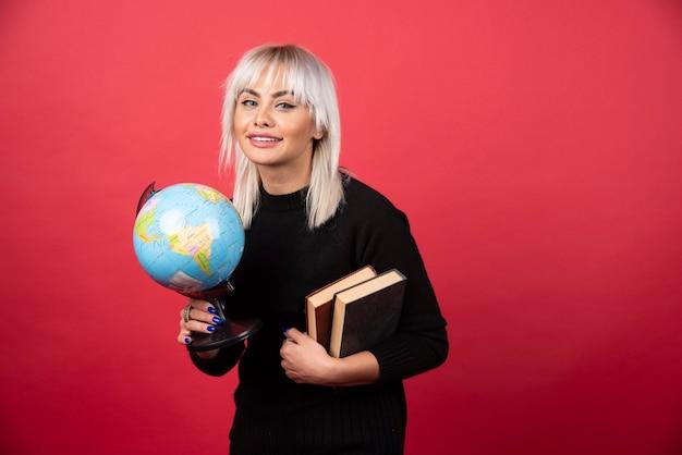 Modèle de jeune femme posant avec un livre et un globe terrestre sur un mur rouge.