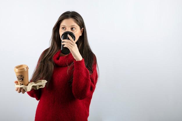 Un modèle de jeune femme en pull rouge tenant deux tasses de café