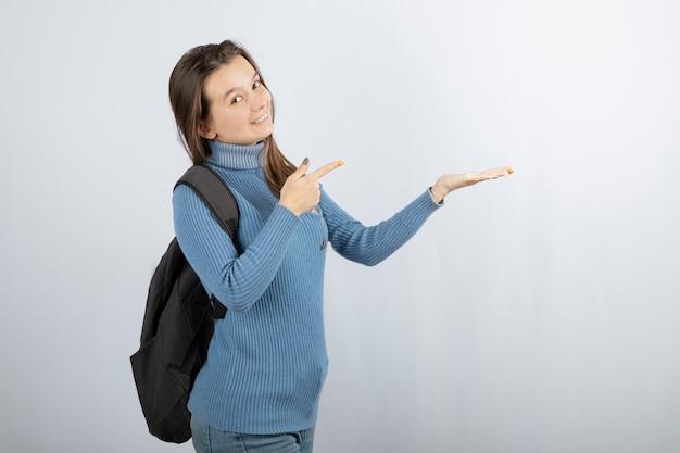 Modèle de jeune femme souriante avec sac à dos pointant sur une main.