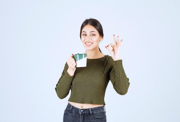 Un modèle de jeune femme souriante tenant une tasse et montrant un geste correct.
