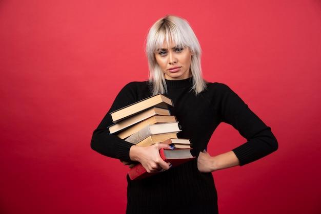 Modèle de jeune femme tenant beaucoup de livres sur un mur rouge.