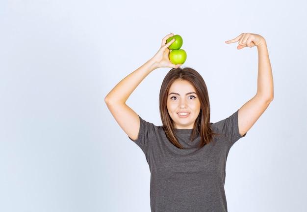 Modèle de jeune femme tenant deux pommes vertes au-dessus et les pointant du doigt.