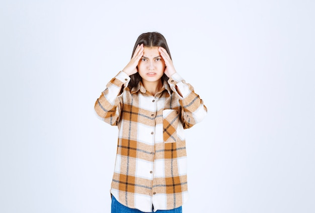 Modèle de jeune fille irritée tenant sa tête et souffrant de douleurs.