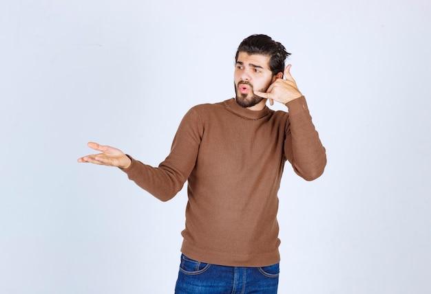 Un modèle de jeune homme debout et pointant ses dents. photo de haute qualité