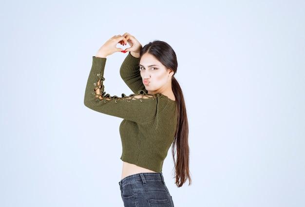 Modèle de jeune jolie femme faisant la forme du symbole du coeur avec les mains.