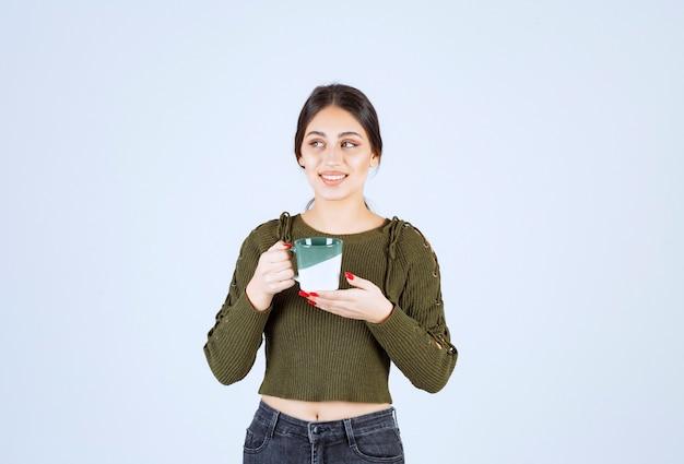 Un modèle de jeune jolie femme tenant une tasse et en détournant les yeux.