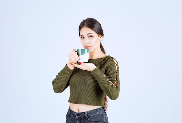 Un Modèle De Jeune Jolie Femme Tenant Une Tasse Et Regardant La Caméra Photo gratuit
