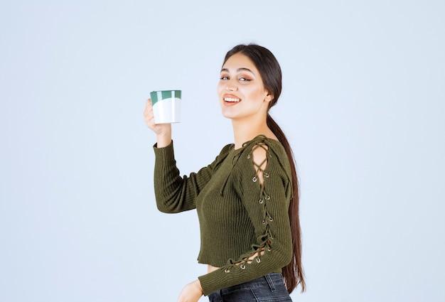 Un modèle de jeune jolie femme tenant une tasse et regardant la caméra