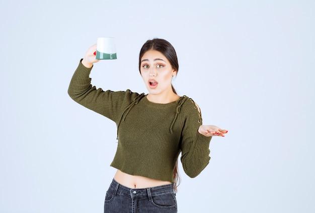 Un modèle de jeune jolie femme tenant une tasse vide et regardant la caméra