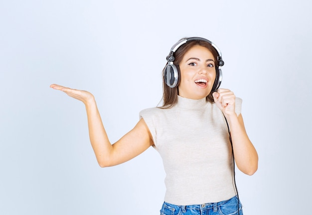 Modèle de jolie femme écoutant de la musique dans les écouteurs et chantant.