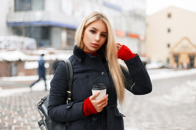 Modèle de jolie jeune femme blonde avec du café dans un manteau de mode avec un sac dans la rue de la ville