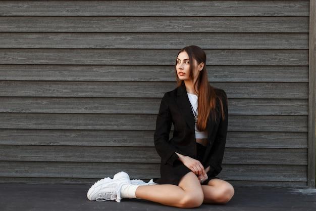 Modèle de jolie jeune femme dans un manteau noir de mode avec des baskets blanches assis près d'un mur en bois