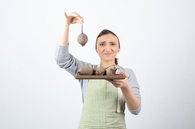 Modèle de jolie jeune femme en tablier tenant une planche de bois avec des betteraves.
