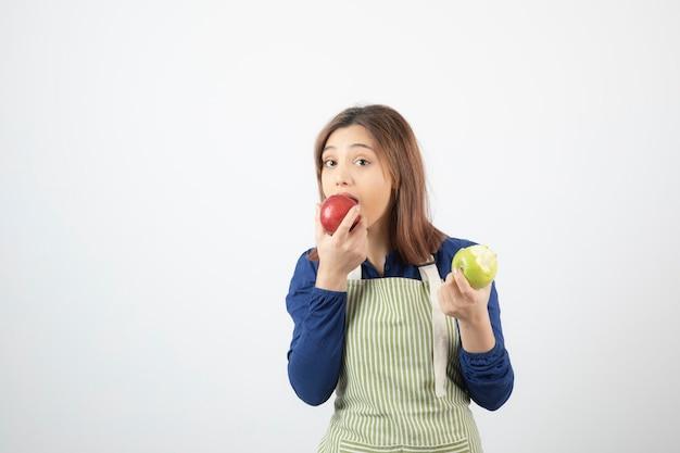 Modèle de jolie jeune femme en tablier tenant des pommes.
