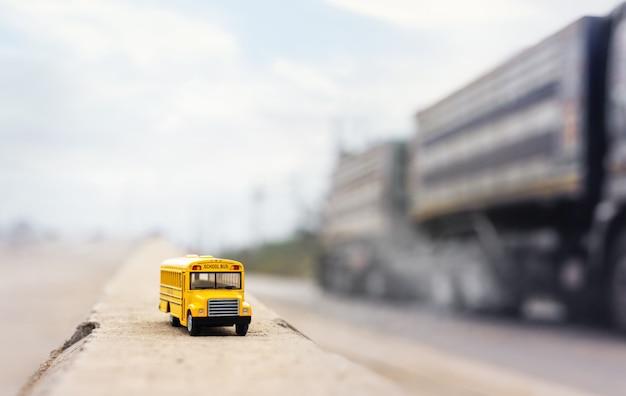 Modèle de jouet d'autobus scolaire jaune sur route de campagne avec camion flou. retour à l'arrière-plan du concept d'école, d'éducation et de transport.