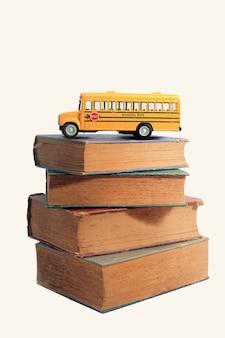 Modèle de jouet d'autobus scolaire jaune et vieux livres. fond vintage.