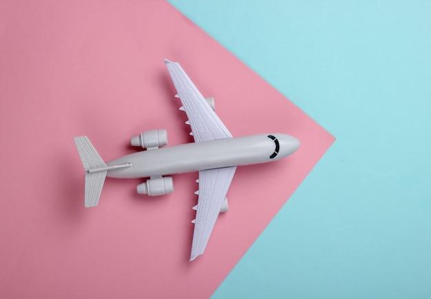 Modèle jouet d'un avion de ligne sur un pastel bleu-rose. le concept de tourisme, de transport aérien, de minimalisme.