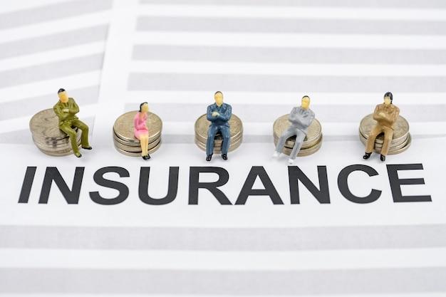 Modèle de jouet de personnes assis sur des piles de pièces de monnaie et sur les contrats d'assurance.