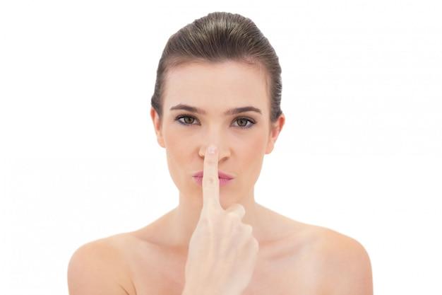 Modèle ludique aux cheveux bruns naturels touchant son nez