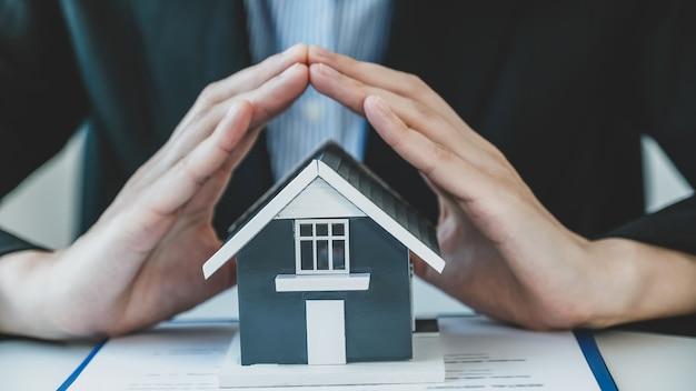 Modèle de maison. un agent immobilier, protégeant un modèle de maison.