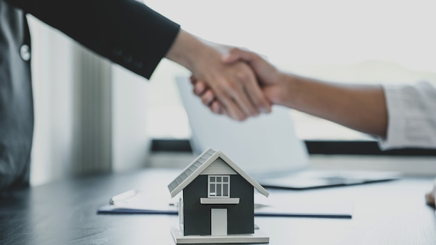 Modèle de maison. les agents immobiliers et les acheteurs se serrent la main après la signature d'un contrat commercial.