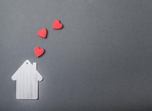 Modèle de maison blanche et fumée en forme de coeurs