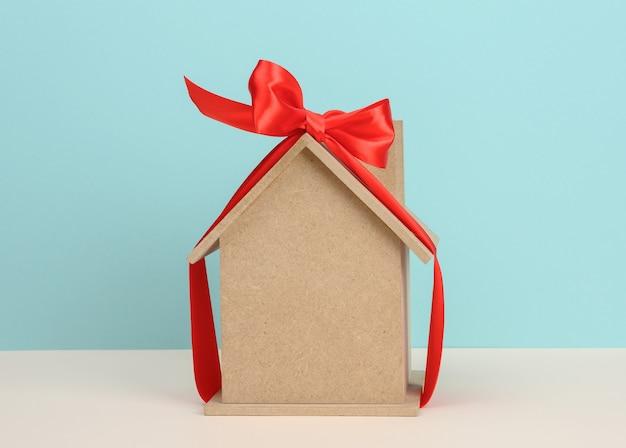 Modèle d'une maison en bois attachée avec un ruban de soie rouge, concept d'achat immobilier, hypothèque
