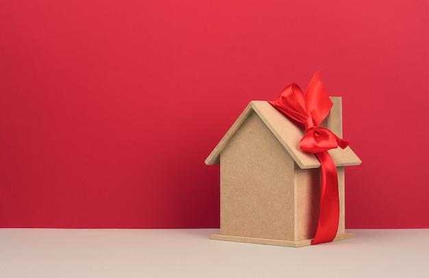 Modèle d'une maison en bois attachée avec un ruban de soie rouge sur fond rouge, concept d'achat immobilier, hypothèque. copier l'espace
