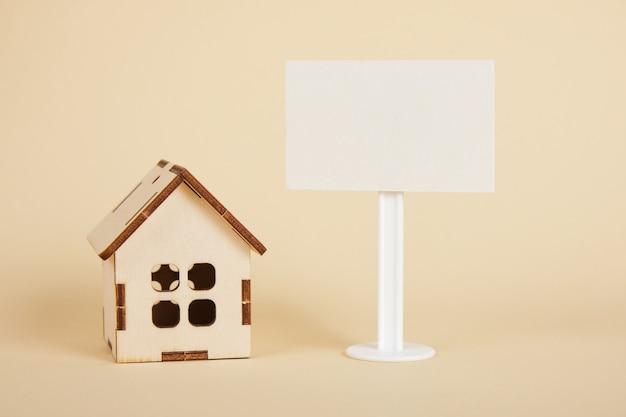 Modèle de maison en bois et blanc signe vierge sur fond beige espace copie concept immobilier
