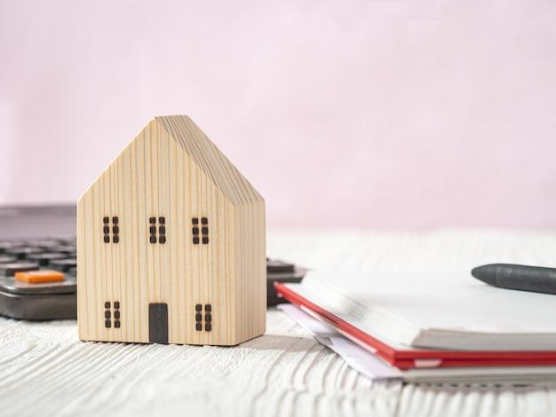 Modèle de maison en bois, calculatrice et livre sur fond de bois blanc. plan d'hypothèque de l'industrie de la maison et stratégie d'économie fiscale
