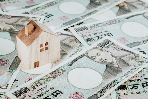 Modèle de maison en bois sur pile de yens japonais. concept immobilier