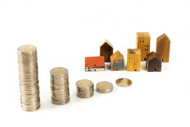 Modèle de maison en bois et rangée de pièces de monnaie sur fond blanc