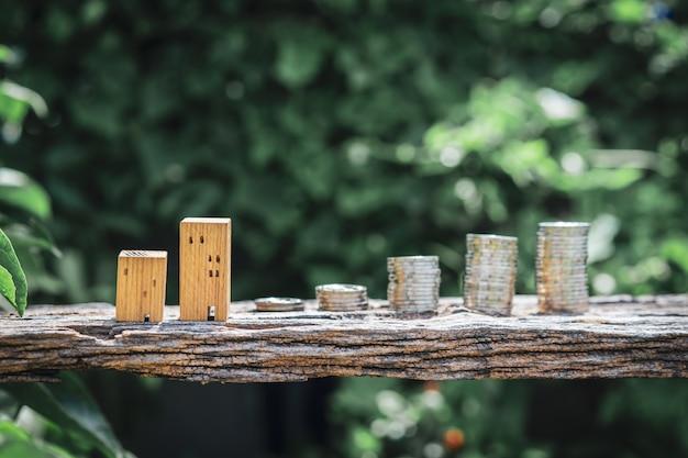 Modèle de maison en bois et rangée de pièces de monnaie sur la table en bois