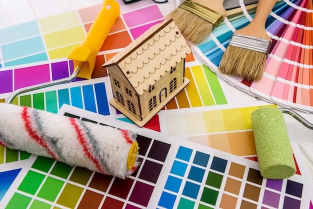 Modèle de maison en bois et rouleau sur palette de couleurs