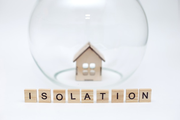 Modèle d'une maison en bois sous un dôme de verre et des lettres en bois avec l'inscription isolation