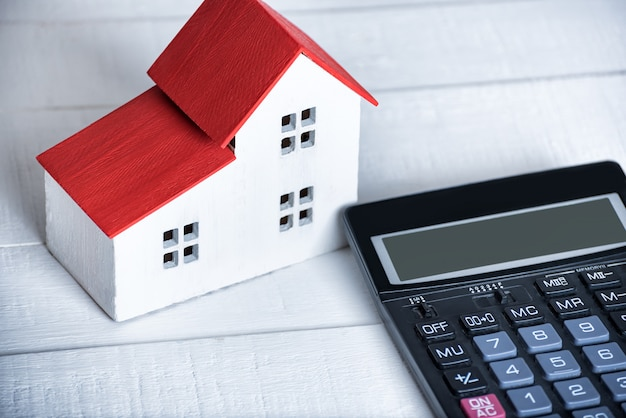 Modèle maison et calculatrice allumés. concept d'achat de maison. fermer