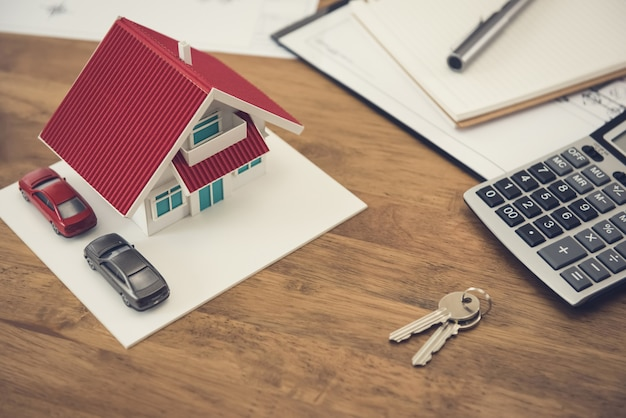 Modèle de maison, clé et calculatrice avec des documents sur la table