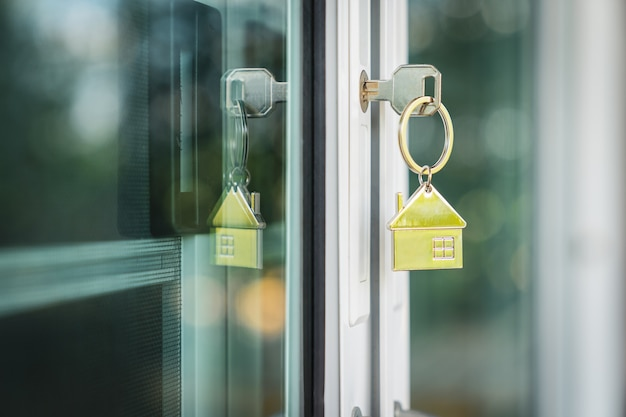 Modèle de maison et clé dans la porte de la maison