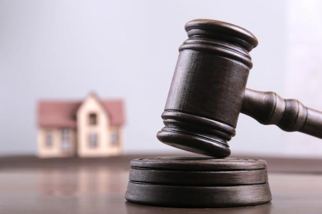 Modèle de maison sur les dollars en argent avec le marteau d'un juge comme financement de fonds hypothécaires et risque d'investissement