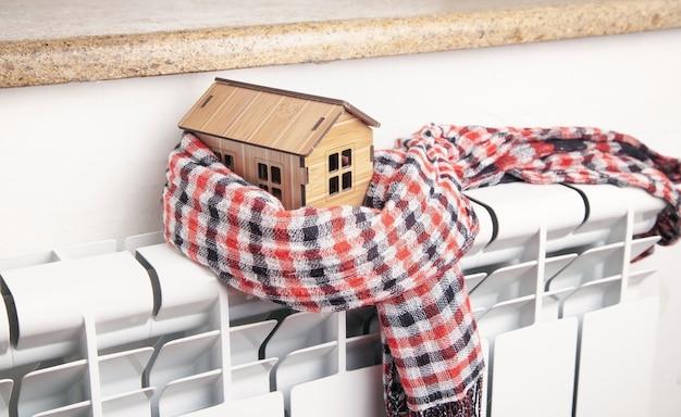 Modèle de maison et écharpe sur radiateur. accueil. l'hiver. énergie. efficacité. chauffage
